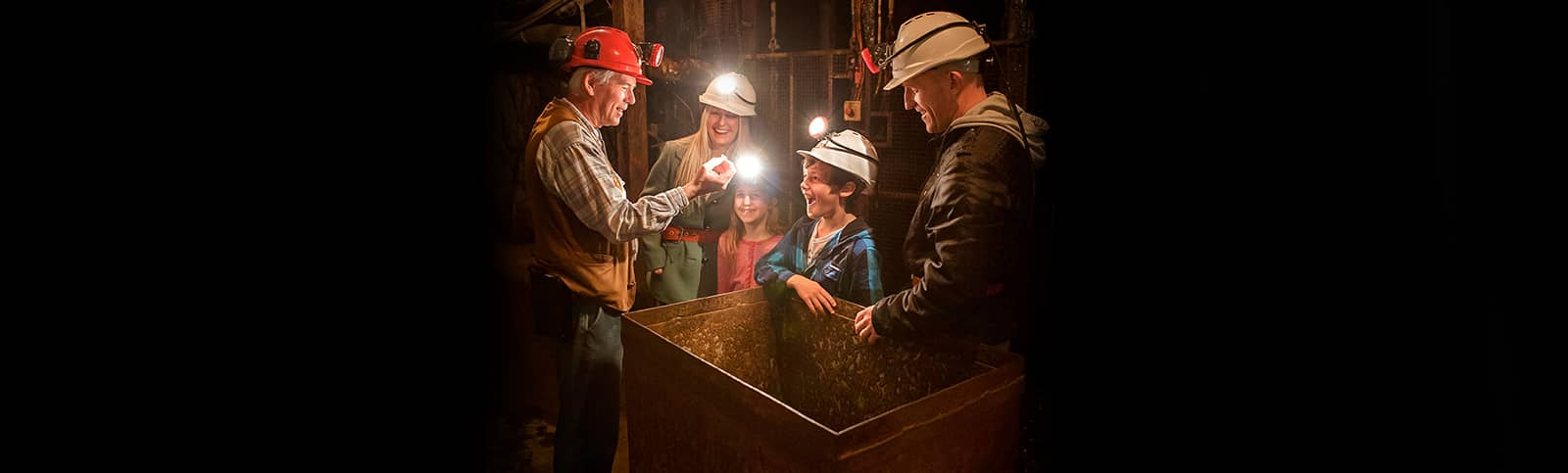 Tour Guide showing family a gold nugget underground on a Mine Experience Tour