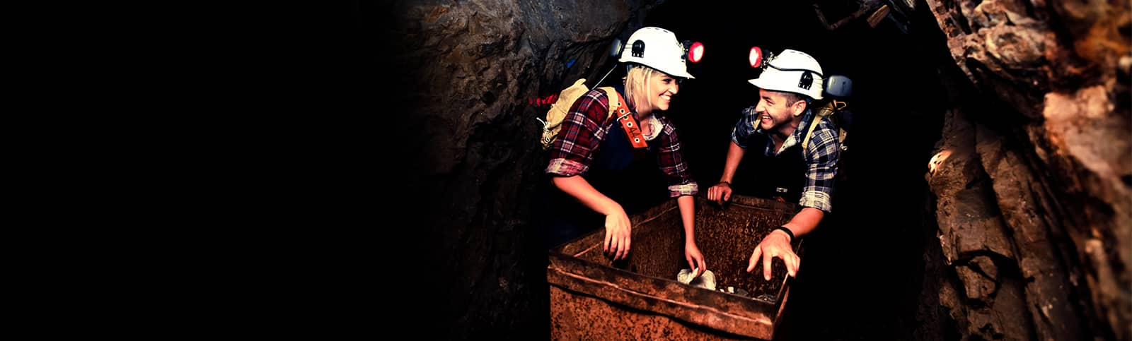 Visitors pushing an Ore Truck on a Nine Levels of Darkness Tour