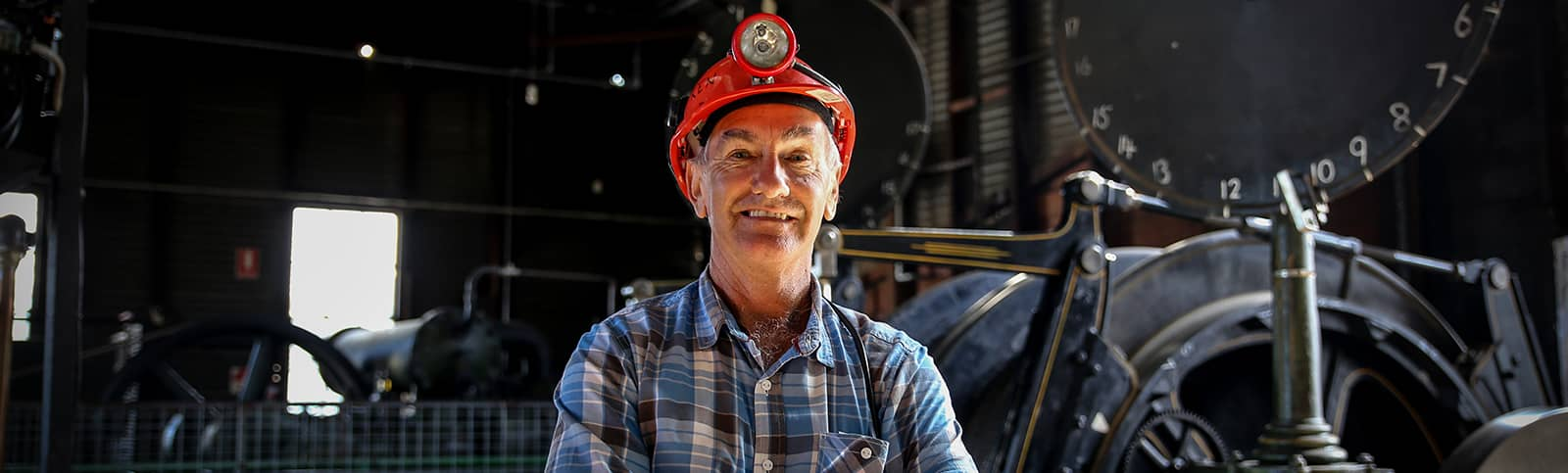 Central Deborah Gold Mine Tour Guide Ken standing in Engine Room with hard hat on