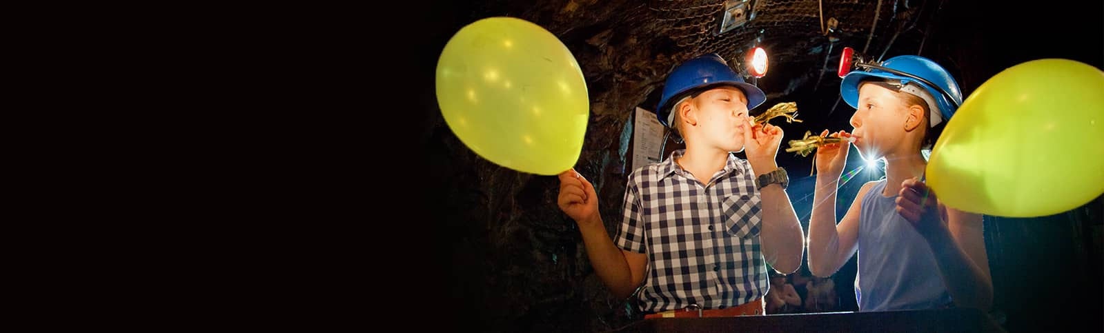 Kids wearing hard hats and holding balloons underground at a Birthday Party