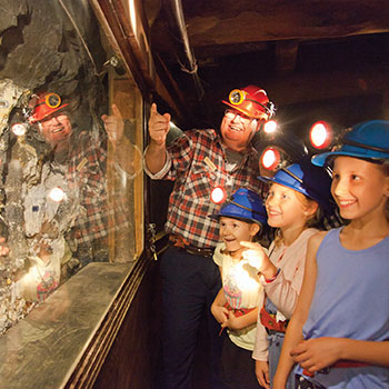 Tour guide showing children gold underground on a Mine Experience