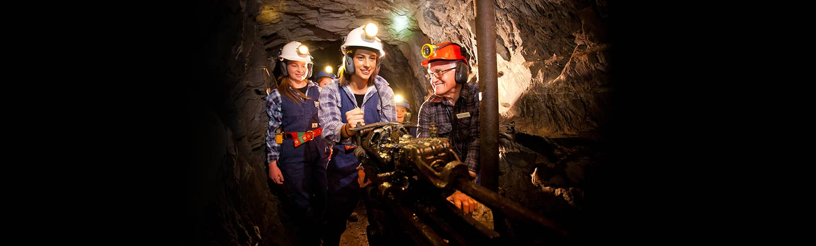 Visitor working a drill on an Underground Adventure Tour
